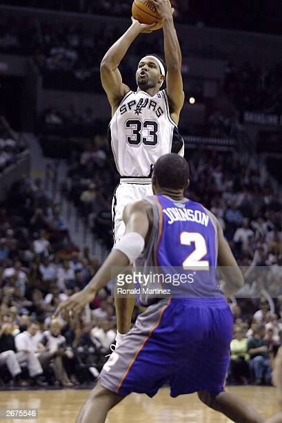 Guard Ron Mercer of the San Antonio Spurs takes a jumpshot over Joe Johnson of the Phoenix Suns on October 28 2003 at the SBC Center in San Antonio...