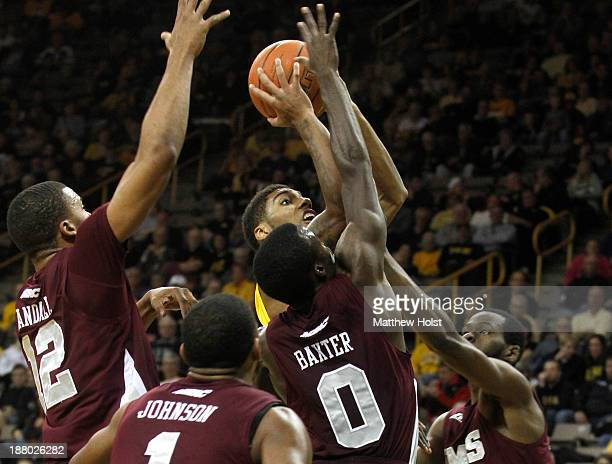 Guard Roy Devyn Marble of the Iowa Hawkeyes shoots during the first half against forward Shane Randall forward Iman Johnson guard Hakeem Baxter and...