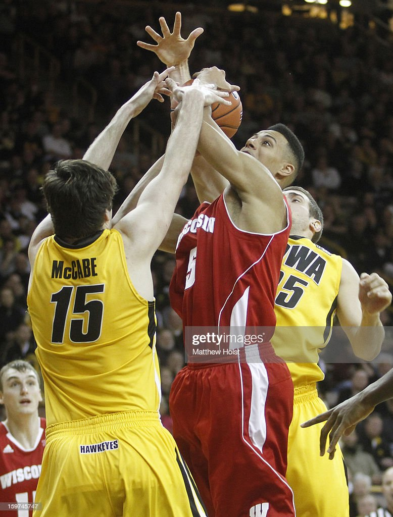Guard Ryan Evans #5 of the Wisconsin Badgers drives to the basket during the first half against forwards Zach McCabe #15 ande Eric May #25 of the Iowa Hawkeyes on January 19, 2013 at Carver-Hawkeye Arena in Iowa City, Iowa. Iowa won 70-66.