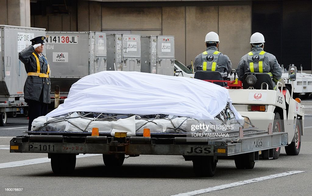 A guard (L) salutes to a coffin containing the last Japanese victim of the Algerian hostage crisis after it was unloaded from a plane at Narita Airport, outside Tokyo on January 26, 2013. The body of the last of 10 Japanese killed in the Algerian hostage crisis arrived in Japan by commercial flight, a day after the bodies of the nine others returned home with seven Japanese survivors. AFP PHOTO / Toru YAMANAKA