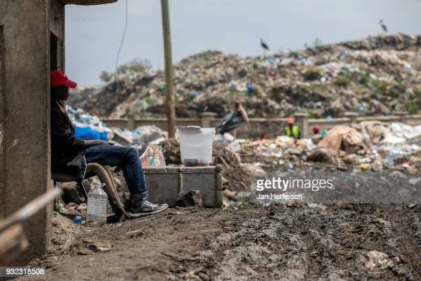 A guard sits in front of the entrance to the Dandora rubbish dump on March 14 2018 in Nairobi Kenya The Dandora landfield is located 8 Kilometer east...