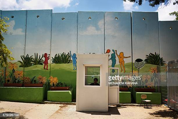 A guard sits outside a kindergarten surrounded by decorated concrete blast walls designed to protect from rocket and mortar fire on June 24 in the...