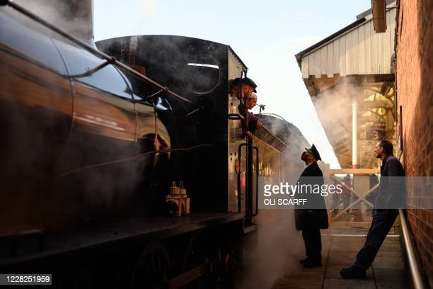 A guard speaks with engine drivers as they prepare a steam train before it runs along the East Lancashire Railway's line from Bury station in...