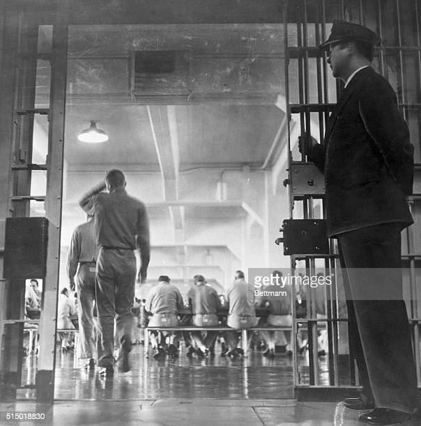 A guard stands by as prisoners enter the Alcatraz mess hall for supper Today most of the men on the Rock are permitted to eat together but in the...