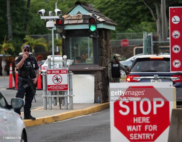 A guard stands by at the Nimitz Gate of Pearl Harbor in Hawaii shortly after a sailor fatally shot two civilians at the Pearl Harbor Naval Shipyard...