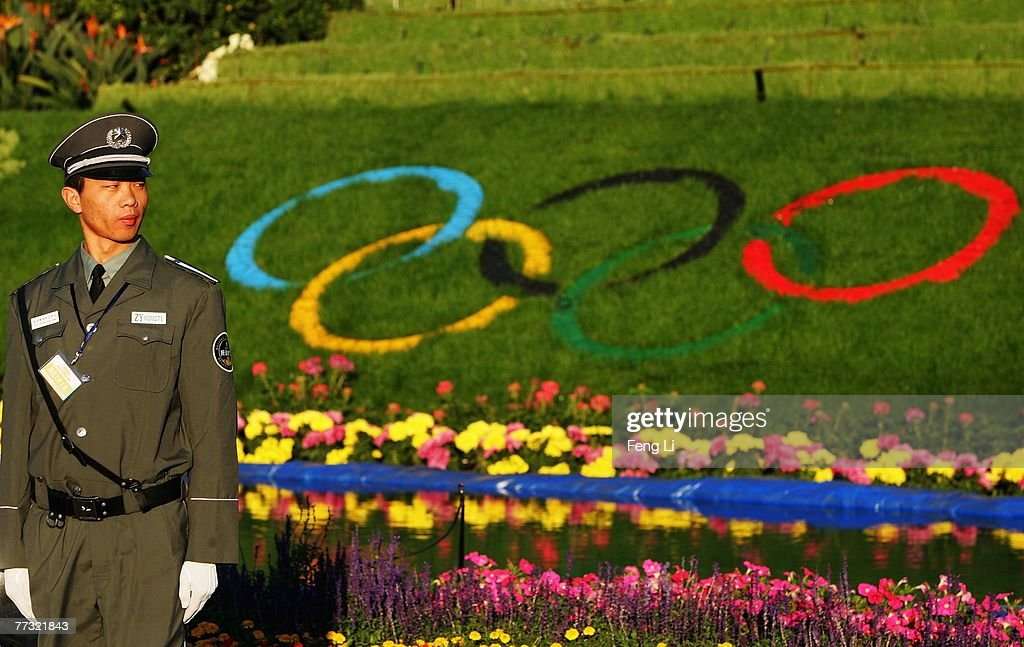 A guard stands in front of flower bed with Olympic pattern at the Tian'anmen Square on October 14, 2007 in Beijing, China. The 17th CPC National Congress, to convene on October 15, will review the Party's work in the past five years and set directions for reform and development of the next stage.