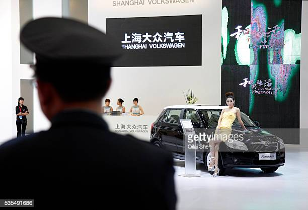 Guard stands near a Shanghai Volkswagen display at the Auto Shanghai 2009 in Shanghai, China, on Monday, April 20, 2009. Automakers from across the...