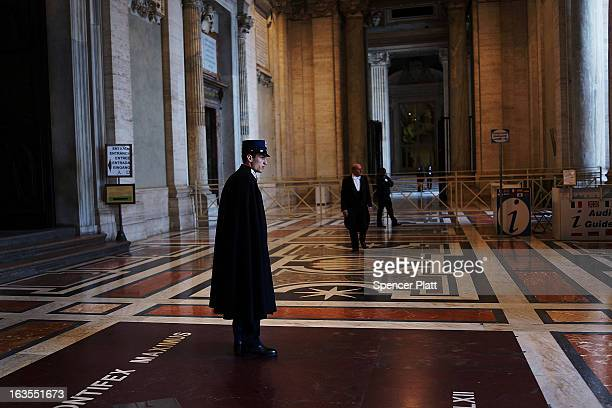 A guard stands near the entrance of St Peter's Basilica during the Pro Eligendo Romano Pontifice Mass at St Peter's Basilica after which Cardinals...