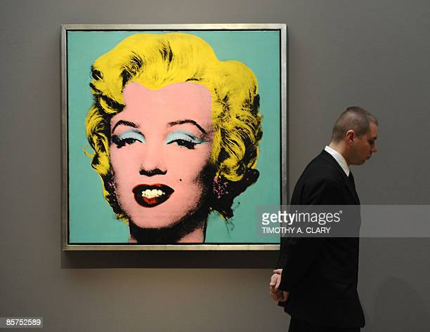 A guard stands near the painting 'Turquoise Marilyn' by Andy Warhol during a media preview on April 1 2009 of a exhibition on loan to Sotheby's New...