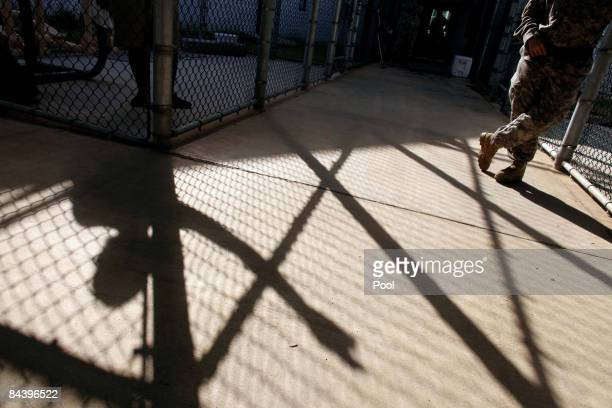 A guard stands near the shadow of a detainee at Guantanamo's Camp 5 detention center at the US Naval Base January 21 2009 in Guantanamo Bay Cuba The...