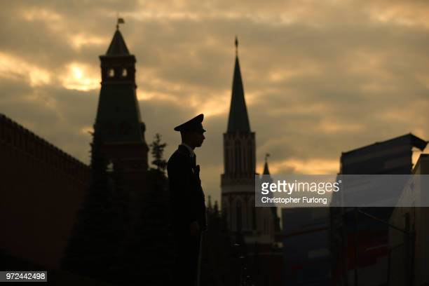 A guard stands next to the Kremlin as people watch perfomers on stage in Red Square during a concert to celebrate 'Russia Day' ahead of the 2018...