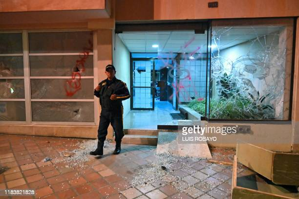 Guard stands outside a vandalised bank after protests during a nationwide strike called by students, unions and indigenous groups to protest against...