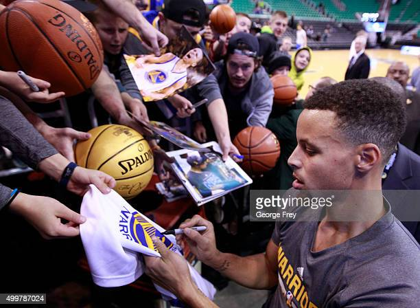 Guard Stephen Curry of the Golden State Warriors signs autographs after warmups before a game against the Utah Jazz at an NBA game November 30 2015...