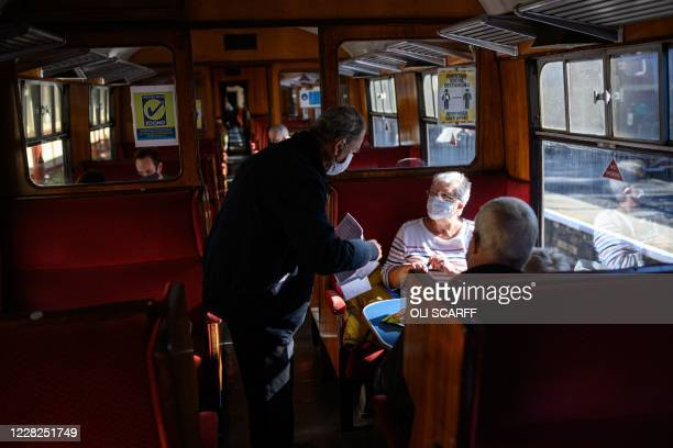 A guard takes the contact details of passengers travelling on a steam train before it runs along the East Lancashire Railway's line from Bury station...