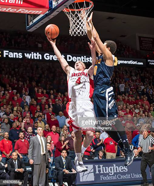 Guard TJ McConnell of the Arizona Wildcats does a layup while being defended by guard Jaron Martin of the UC Irvine Anteaters at McKale Center on...