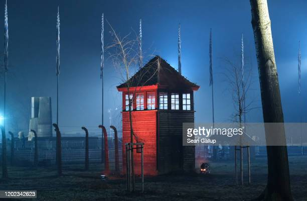Guard tower stands illuminated at the former Auschwitz-Birkenau concentration camp near the Auschwitz Memorial during the official ceremony to mark...