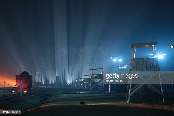 Guard towers and a railway car stand on the illuminated grounds of the former Auschwitz-Birkenau concentration camp during the official ceremony to...
