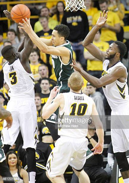 Guard Travis Trice of the Michigan State Spartans drives to the basket against guard Peter Jok guard Mike Gesell and center Gabriel Olaseni of the...