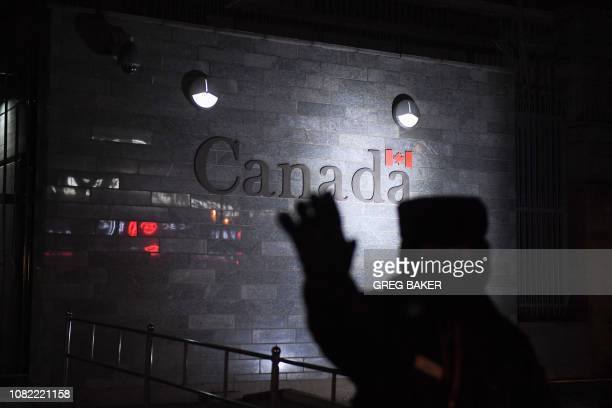 Guard tries to block photos being taken as he patrols outside the Canadian embassy in Beijing on January 14, 2019. - A Chinese court sentenced a...