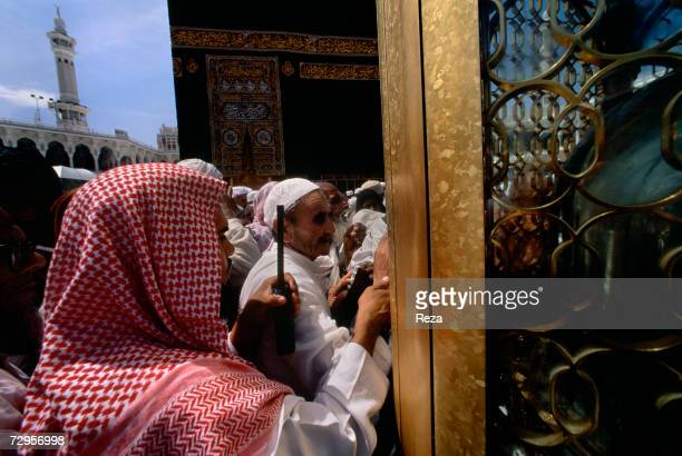 A guard tries to control the flow of worshippers around the Maqam Ibrahim next to the Kaaba Islam's most sacred sanctuary and pilgrimage shrine in...