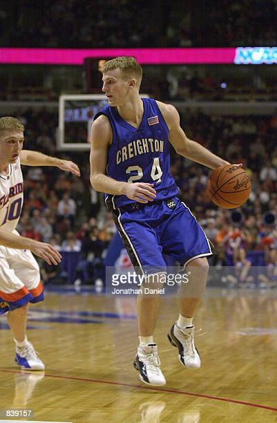 Guard Tyler McKinney of the Creighton Bluejays dribbles the ball on the perimeter against guard Brett Nelson of the Florida Gators during the first...