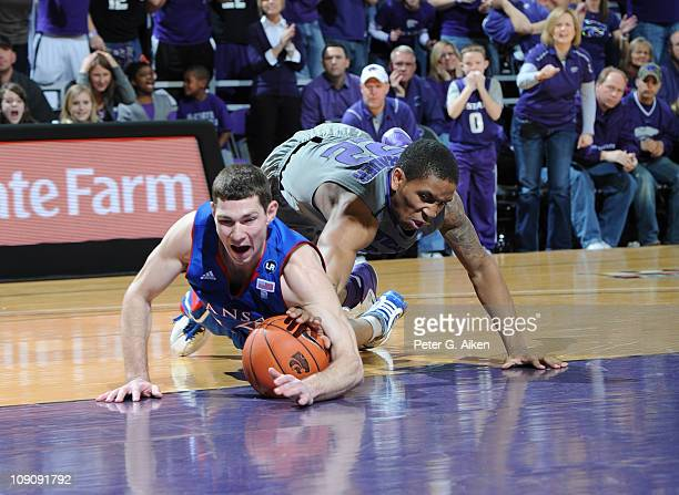 Guard Tyrel Reed of the Kansas Jayhawks dives for a loose ball with guard Rodney McGruder of the Kansas State Wildcats during the first half on...