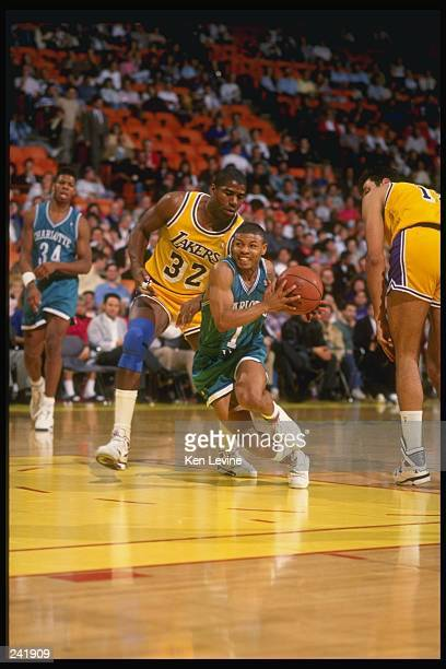 Guard Tyrone Bogues of the Charlotte Hornets keeps the ball away from guard Magic Johnson of the Los Angeles Lakers during a game at the Great...