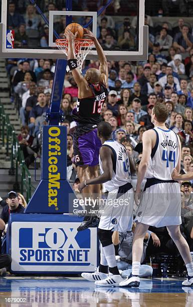 Guard Vince Carter of the Toronto Raptors dunks against forward Walt Williams of the Dallas Mavericks during the game at American Airlines Center on...