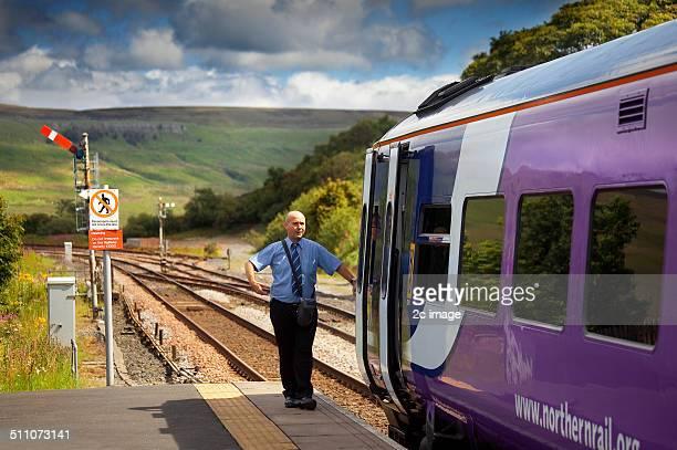 A guard waits to depart his train at Garsdale head Cumbria England