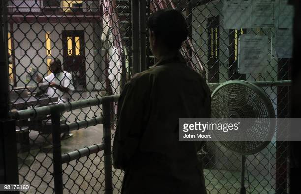A guard watches as a detainee reads library books at Camp 6 in the Guantanamo Bay detention center on March 30 2010 in Guantanamo Bay Cuba US...