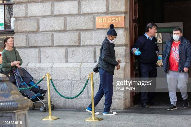 A guard wers gloves as a precautionary measure against covid19 as he counts people in and out of The General Post Office in the Temple Bar district...