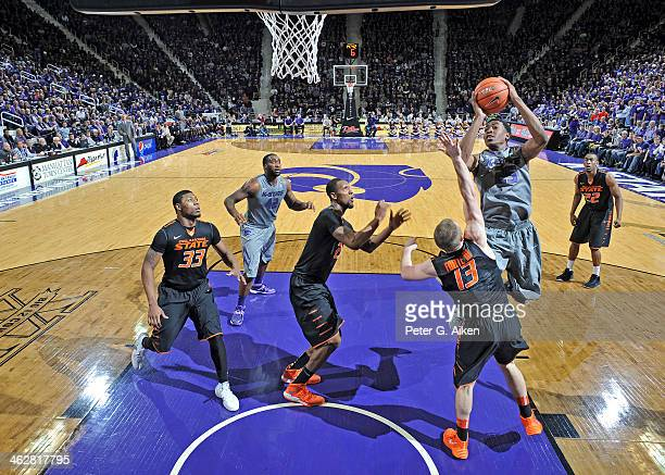 Guard Wesley Iwundu of the Kansas State Wildcats drives to the basket over guard Phil Forte of the Oklahoma State Cowboys during the first half on...