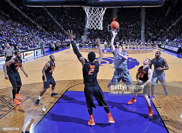 Guard Will Spradling of the Kansas State Wildcats drives to the basket between defenders Phil Forte and Le'Bryan Nash of the Oklahoma State Cowboys...