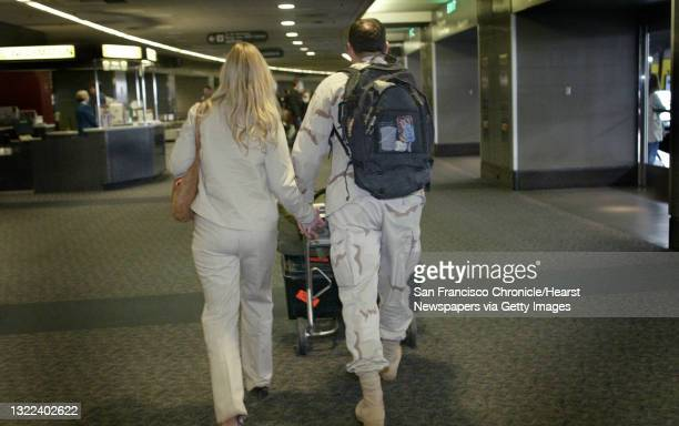 Guard02105_ls.jpg From left: Lori Hancock and Capt. Charles Hancock hold hands as leave the airport with his luggage on the way to the elevator....