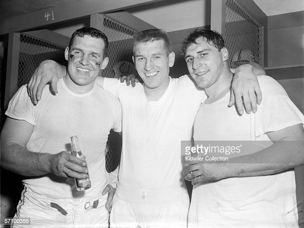 Guard/defensive lineman/kicker Steve Myhra quarterback Johnny Unitas and runningback Alan Ameche of the Colts celebrate the victory following the NFL...