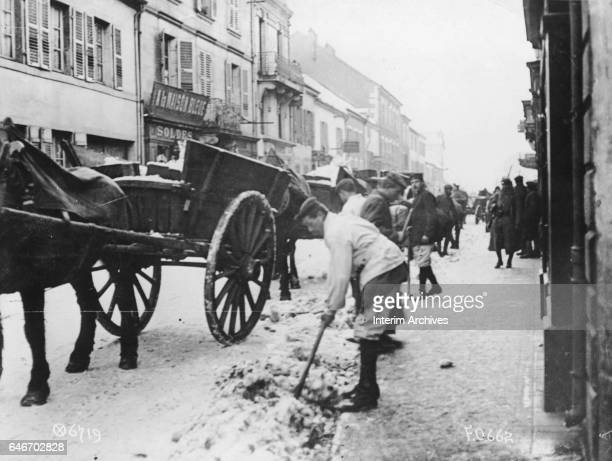 Guarded by French soldiers, German World War I prisoners of war shovel snow from a street in an unspecified town in the Haute-Saone district, France,...
