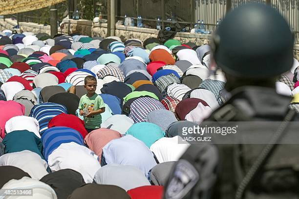 Guarded by Israeli policemen Muslim worshipers pray on the streets of the Wadi alJoz neighborhood in east Jerusalem on July 31 following restrictions...