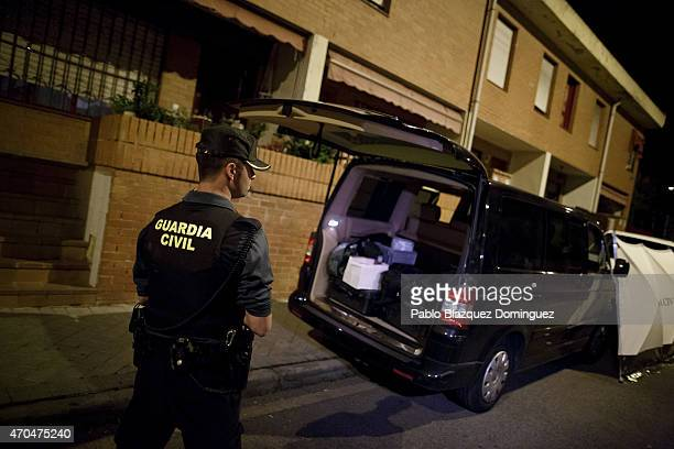 Guardia Civil member stands watch over the investigators' van after searching in the presence of a suspect arrested in connection to the...