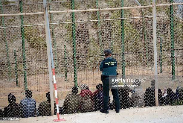 Guardia Civil Officer watches detained African migrant after scaling the fence at the border between Morocco and the North African Spanish enclave of...