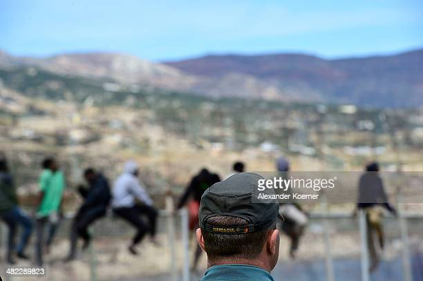 Guardia Civil Officers watch African migrants attempt to scale the fence at the border between Morocco and the North African Spanish enclave of...