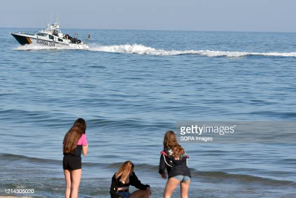 Guardia civil police boat patrols the shoreline while girls play in the sand on Calafell beach during the final confinement of Phase One Calafell is...