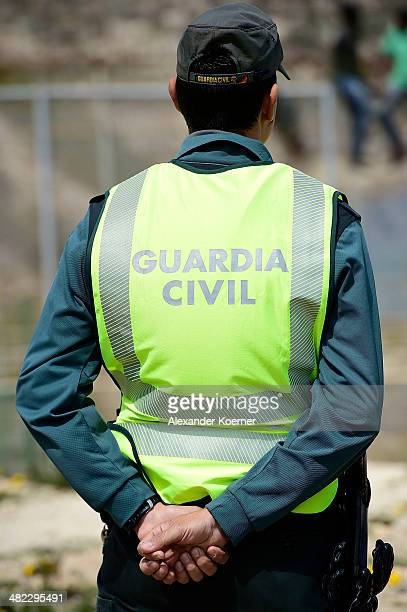 Guardia Civil Police Officer watch esAfrican migrants who attemped to scale the fence at the border between Morocco and the North African Spanish...