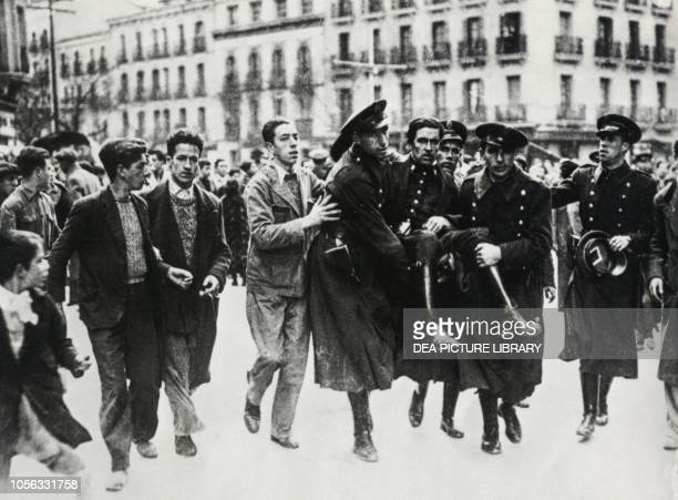 Guardia de Asalto injured during a street clash being carried from the field by his comrades Barcelona, Spain, Spanish Civil War, 20th century.