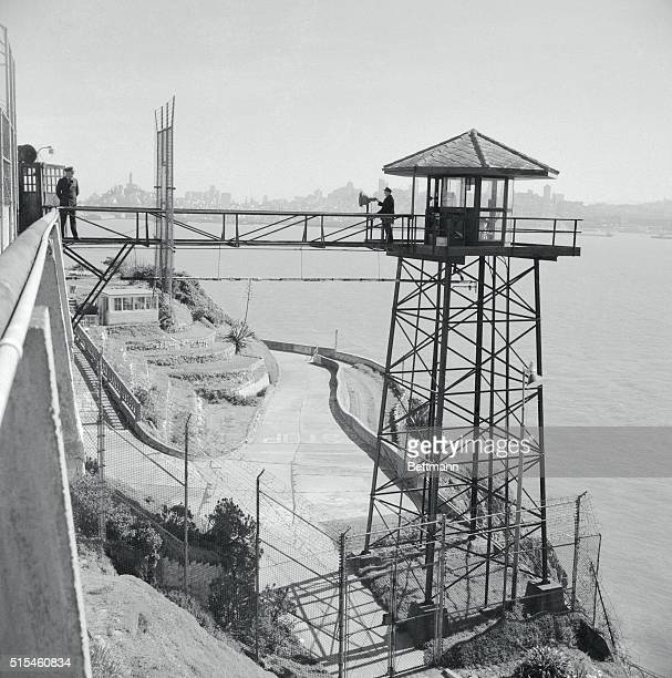 Guards are eternally vigilant on the high towers overlooking the prison which claims to be escapeproof San Francisco's skyline can be seen across the...