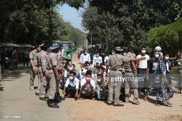 Guards check freed prisoners before leaving the Insein in Yangon on February 12, 2021 as Myanmar's military regime ordered the release of more than...