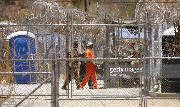 Guards escort a prisoner through Camp X-Ray April 24, 2002 in Guantanamo Bay, Cuba. Some 300 alleged Taliban and al Qaeda detainees have been brought...