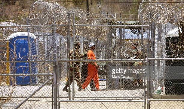 Guards escort a prisoner through Camp XRay April 24 2002 in Guantanamo Bay Cuba The military announced September 25 2003 that it would be is...
