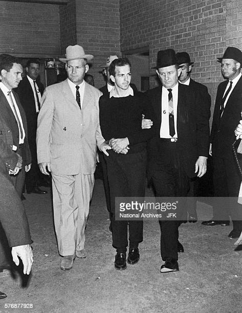 Guards escort Lee Harvey Oswald during a press conference two days after his arrest in conjunction with the assassination of President Kennedy Oswald...