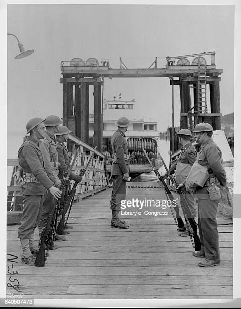 Guards in the foreground look on as a ferryboat leaves the Bainbridge Landing with Japanese evacuees destined for Manzanar California Bainbridge...