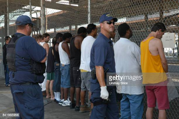 Guards line up male prisoners before fenced bus gate makeshift intake cell at Greyhound Station nicknamed Angola South in mandatorily evacuated city...